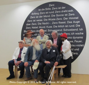 Zero artists (or spouses) with the Zero Manifesto on wall behind them at the Amsterdam Stedelijk Museum, (4 July 2015). Back row l. to r.: Elizabeth Goldring Piene, Christian Megert, Jan Henderikse and unidentified woman. Front row l. to r.: unidentified man, herman de vries and Uli Pohl.